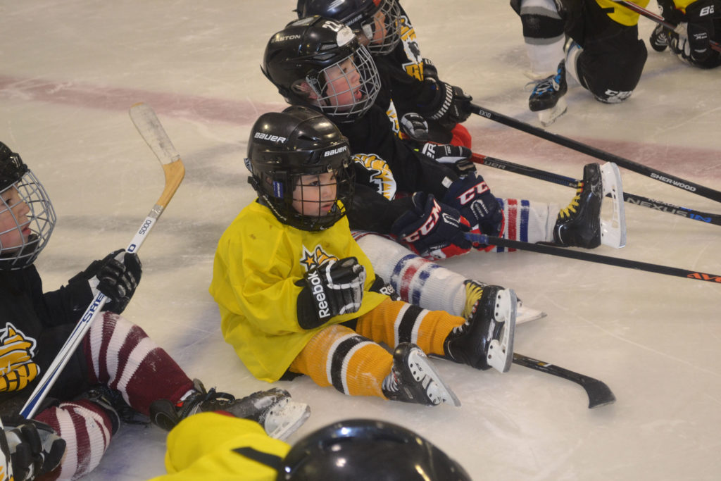 Children in hockey attire on ring